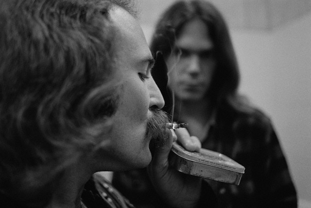 12 Jul 1970, USA --- Musician David Crosby smokes a cigarette while Neil Young looks on. They are in a backstage bathroom. --- Image by © Henry Diltz/CORBIS