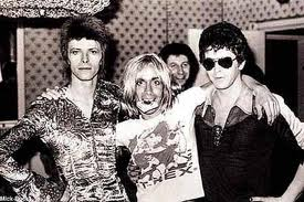 Four glammy, glittery icons party down in the early '70s (from left): David Bowie, Iggy Pop, and Lou Reed. The fourth? Why, Marc Bolan of course, as seen on Iggy's T. Rex T-shirt!